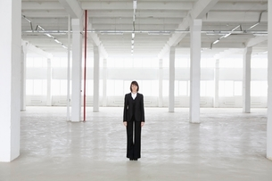 Business woman stands in empty warehouseの写真素材 [FYI03636060]
