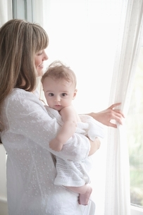 Mother stands looking through window while holding a babyの写真素材 [FYI03636175]