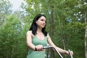 Young woman stands with bicycle in woodlandの写真素材 [FYI03636253]