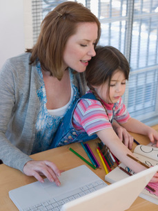 Mother Using Laptop While Daughter Colorsの写真素材 [FYI03636283]