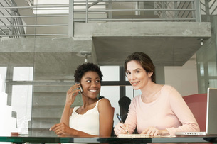 Two businesswomen in office  one using mobile phone  portrの写真素材 [FYI03636322]