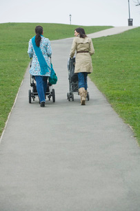 Back view of two mothers pushing strollers in parkの写真素材 [FYI03636363]