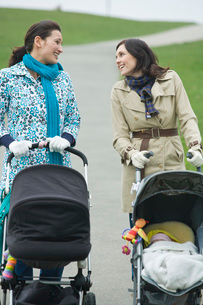 Two mothers with strollers in park having chatの写真素材 [FYI03636364]