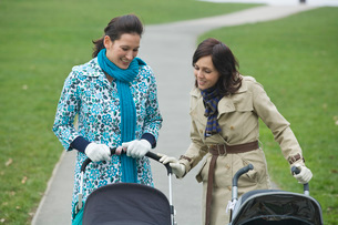 Two mothers in park looking at their babies in strollersの写真素材 [FYI03636366]