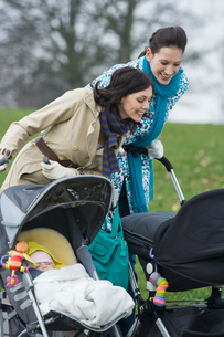 Two mothers in park looking at their babies in strollersの写真素材 [FYI03636368]