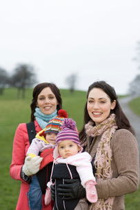 Two mothers with babies in baby carriers in parkの写真素材 [FYI03636372]