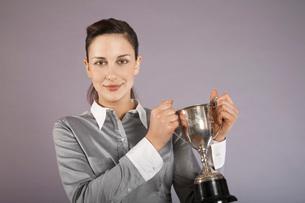 Businesswoman holding trophy  portraitの写真素材 [FYI03636406]