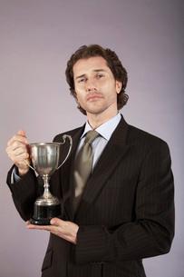Businessman holding trophy  portraitの写真素材 [FYI03636411]