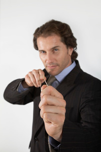 Businessman aiming rubber band  on white background  portrの写真素材 [FYI03636420]
