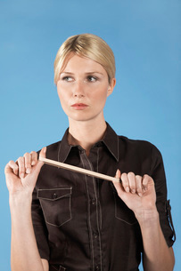 Businesswoman stretching rubber band  on blue backgroundの写真素材 [FYI03636429]