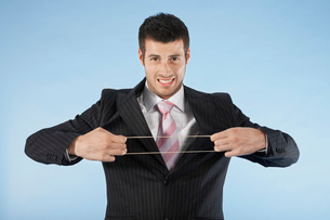 Businessman stretching rubber band  on blue background  poの写真素材 [FYI03636433]