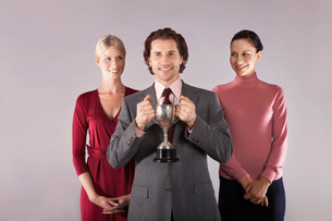 Businessman holding trophy with female colleagues  portraiの写真素材 [FYI03636436]