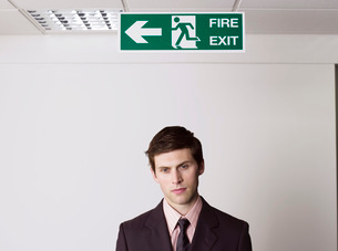 Young businessman standing under exit signの写真素材 [FYI03636445]