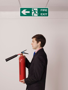 Businessman holding fire extinguisher under exit signの写真素材 [FYI03636447]