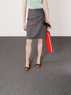 Businesswoman holding fire extinguisher  low sectionの写真素材 [FYI03636451]
