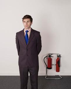 Businessman standing near fire extinguisherの写真素材 [FYI03636452]