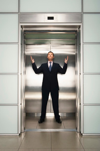 Businessman arms raised in Elevator  front viewの写真素材 [FYI03636465]