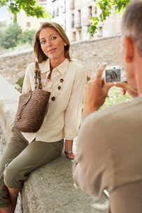 Man taking picture of partner on wall in Granada  Spain  bの写真素材 [FYI03636553]