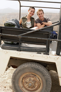 Young couple sitting in back of four wheel drive car in deの写真素材 [FYI03636580]