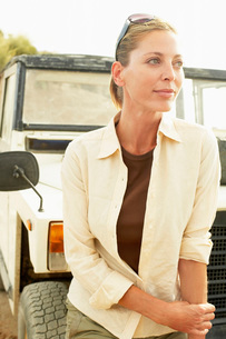 Woman standing in front of four wheel drive car  outdoorsの写真素材 [FYI03636581]