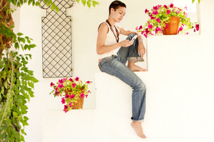 Woman Sitting on wall in garden  using mobile phone.の写真素材 [FYI03636583]