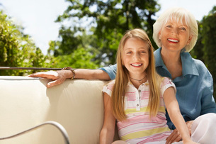 Grandmother and granddaughter on sofa in back yard  portraの写真素材 [FYI03636643]