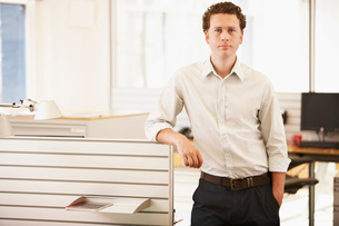 Mid-adult male office worker standing by cubicle  portraitの写真素材 [FYI03636668]