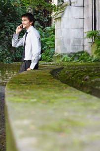 Businessman on cell phone leaning against wall in parkの写真素材 [FYI03636726]