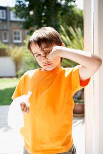 Boy with cold in backyard rubbing eyesの写真素材 [FYI03636730]