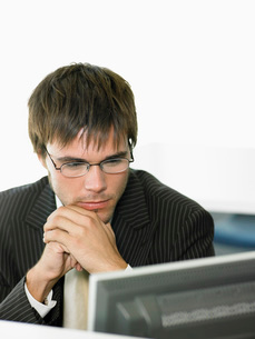 Serious Businessman looking at computer screen in officeの写真素材 [FYI03636750]