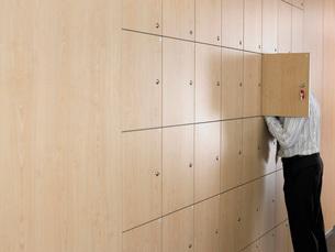 Businessman putting head in small lockerの写真素材 [FYI03636760]