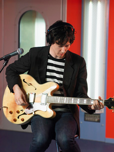 Young man playing guitar in recording studio  portraitの写真素材 [FYI03636788]