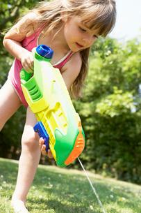 Little girl in park shooting water pistol into grassの写真素材 [FYI03636811]