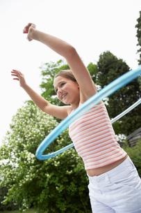 Girl in backyard playing with hula hoopの写真素材 [FYI03636815]