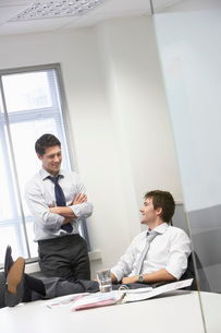 Two happy businessmen relaxing and talking in officeの写真素材 [FYI03636838]