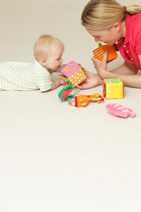 Mother and child playing with toys on floorの写真素材 [FYI03636871]