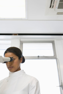 Female scientist using microscope in laboratoryの写真素材 [FYI03636886]