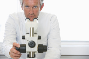 Scientist working behind microscope in laboratoryの写真素材 [FYI03636887]