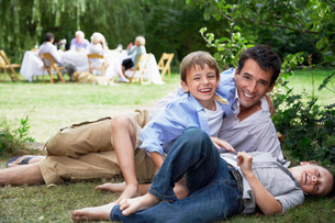 Father and two sons (7-10) having fun on grass in gardenの写真素材 [FYI03636956]