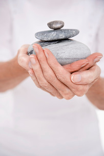 Woman Holding Pile of Stones  mid sectionの写真素材 [FYI03636968]