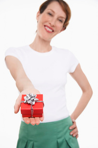 Woman offering small gift wrapped presentの写真素材 [FYI03636974]