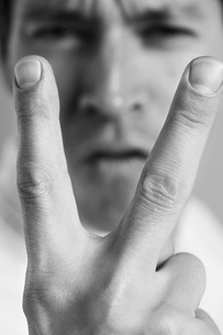 Man holding up two fingers  close-up  black and whiteの写真素材 [FYI03637001]