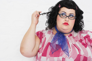 Overweight Woman twisting strand of hair  portraitの写真素材 [FYI03637078]