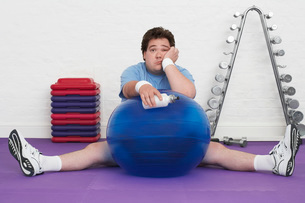 Overweight Man sitting on floor with exercise ball in healの写真素材 [FYI03637083]