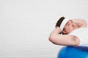 Overweight Man doing sit-ups on Exercise Ballの写真素材 [FYI03637084]