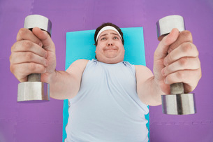 Overweight Man lying down Lifting dumbbells  overhead viewの写真素材 [FYI03637099]