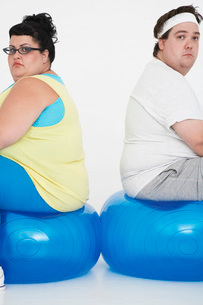 Unhappy overweight man and woman sitting back to back on eの写真素材 [FYI03637105]