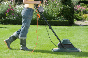Woman Mowing Lawn With electric Lawn Mowerの写真素材 [FYI03637116]