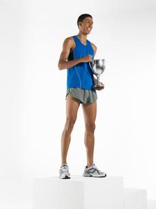Athlete standing  holding trophyの写真素材 [FYI03637136]