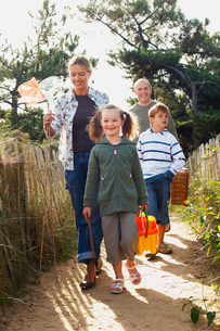 Vacationing family walking on track to beachの写真素材 [FYI03637145]